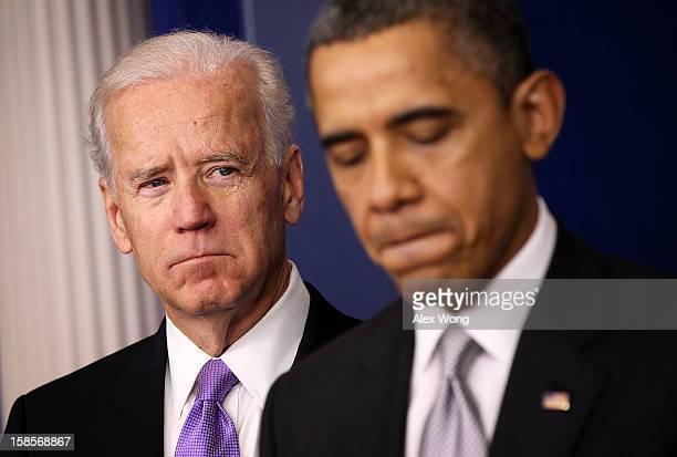 President Barack Obama speaks as Vice President Joseph Biden listens during an announcement on gun reform in the Brady Press Briefing Room of the...