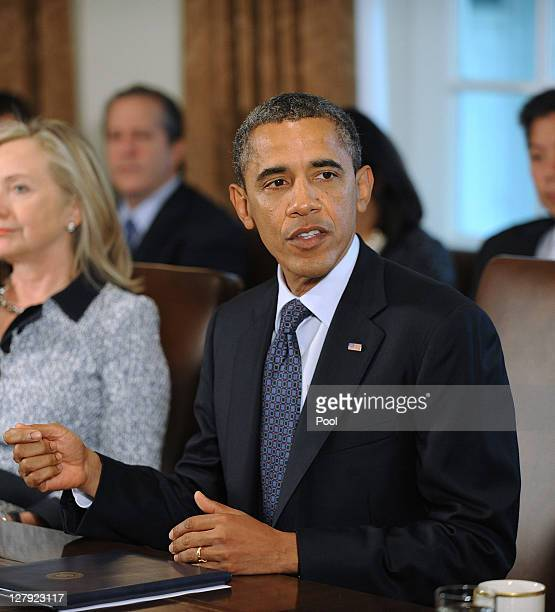 S President Barack Obama speaks during a Cabinet meeting as US Secretary of State Hillary Clinton listens in the Cabinet Room October 3 2011 at the...
