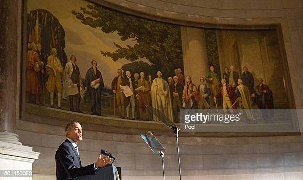 S President Barack Obama speaks during a naturalization ceremony for new US citizens beneath a painting of America's founding fathers at the National...