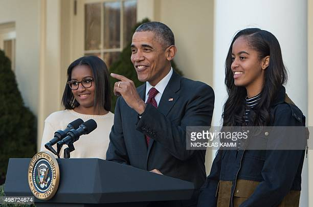 US President Barack Obama speaks next to daughters Malia and Sasha after 'pardoning' the National Thanksgiving Turkey in the Rose Garden at the White...