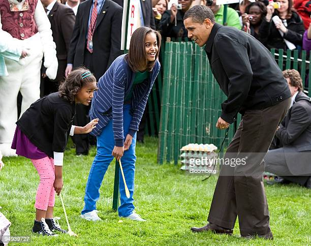 S President Barack Obama speaks to his daughters Malia center and Sasha as they take part in the Easter Egg Roll on the South Lawn of the White House...