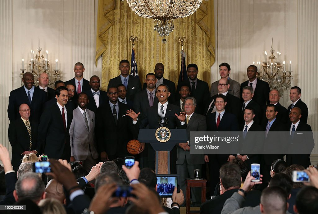 President Barack Obama (C) speaks while flanked by members of the Miami Heat during an event to honor the NBA champions in the East Room at the White House on January 28, 2013 in Washington, DC. President Barack Obama congratulated the 2012 NBA champions for claiming their third NBA Championship by beating the Boston Celtics.