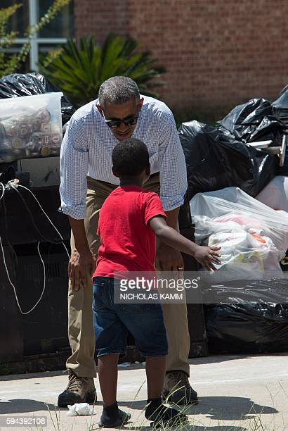 President Barack Obama speaks with 6-year-old Jacolson Kelley as he tours a flood-affected area in Baton Rouge, Louisiana, on August 23, 2016. Fresh...
