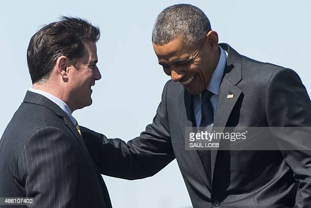 US President Barack Obama speaks with Arizona Governor Doug Ducey upon arrival on Air Force One at Phoenix Sky Harbor International Airport in...