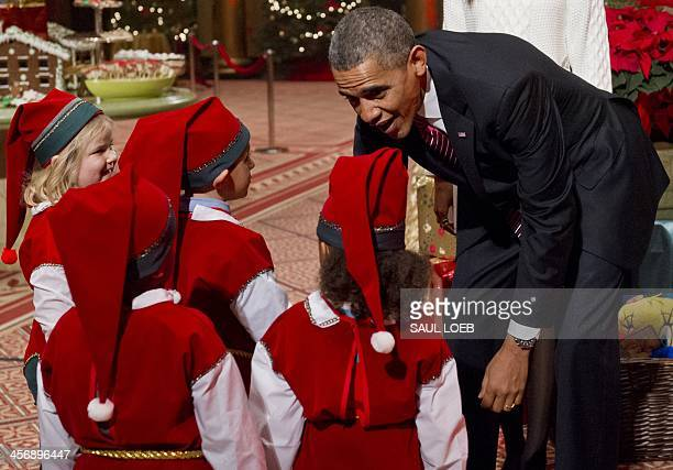 President Barack Obama speaks with children dressed as elves, who are or were patients at Children's National Medical Center as they present donated...