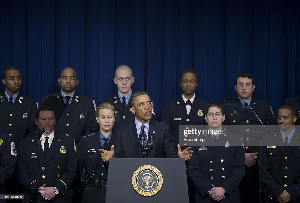 U.S. President Barack Obama speaks with emergency responders behind him in the South Court Auditorium of the Eisenhower Executive Building next to the White House in Washington, D.C., U.S., on Tuesday, Feb. 19, 2013. Obama stepped up pressure on Congress to avert 'brutal' automatic $1.2 trillion in budget cuts set to kick in March 1, saying it would harm the economy and curtail vital services. Photographer: Andrew Harrer/Bloomberg via Getty Images