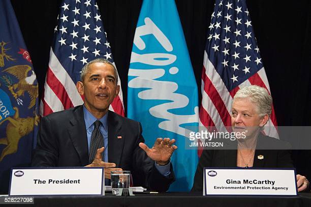 US President Barack Obama speaks with EPA Administrator Gina McCarthy during a meeting at the Food Bank of Eastern Michigan in Flint Michigan May 4...