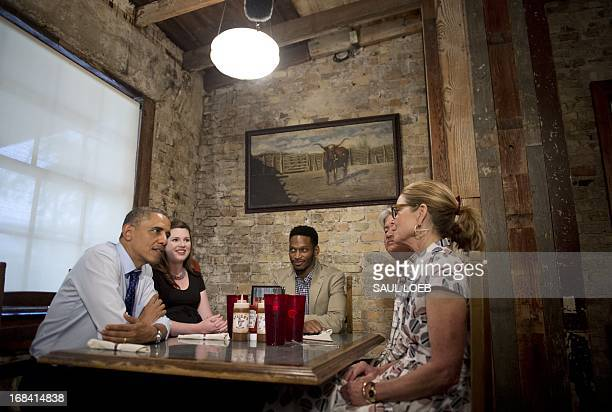 US President Barack Obama speaks with local residents about jobs and the economy while eating lunch at Stubbs BarBQ in Austin Texas May 9 2013 Seated...