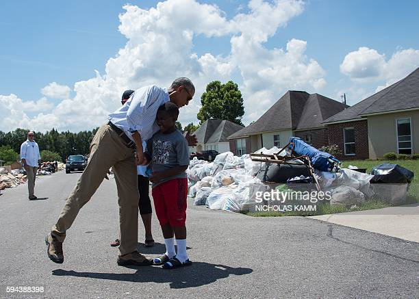President Barack Obama speaks with residents as he tours a flood-affected area in Baton Rouge, Louisiana, on August 23, 2016. President Barack Obama...