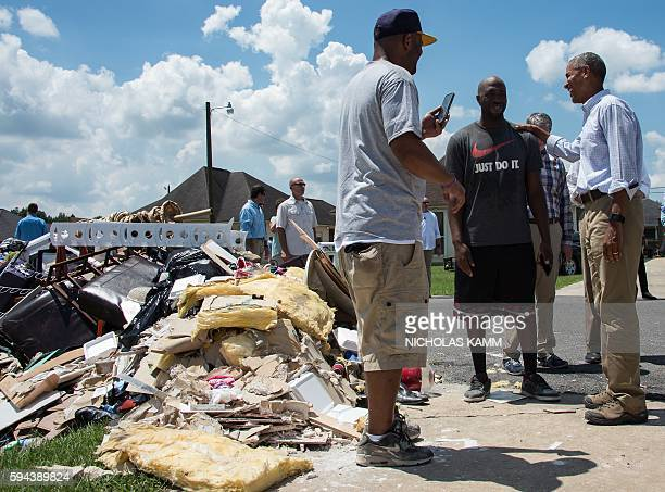 President Barack Obama speaks with residents as he tours a flood-affected area in Baton Rouge, Louisiana, on August 23, 2016. / AFP / NICHOLAS KAMM
