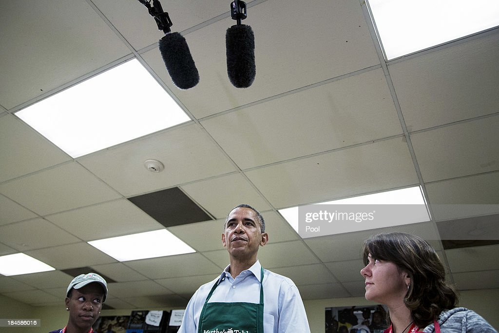 U.S. President Barack Obama (C) speals while visiting with furloughed federal workers Health and Human Services employee Chantelle Burton (L) and U.S. Census Burea employee Dolly Garcia , while they volunteer at a Martha's Table kitchen on October 14, 2013 in Washington, D.C. During a statement, Obama called on congress to end the budget stalemate and allow federal employees to return to work.