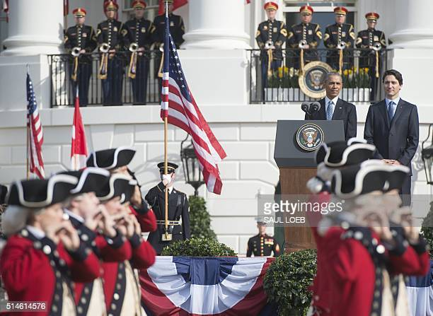 US President Barack Obama stands alongside Canadian Prime Minister Justin Trudeau as they review the troops during a State Arrival ceremony on the...