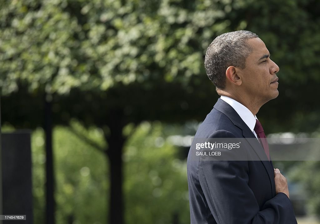 US President Barack Obama stands during the American National Anthem after laying a wreath at the Korean War Veterans Memorial to commemorate the 60th anniversary of the signing of the Armistice that ended the Korean War, during a ceremony in Washington, DC, July 27, 2013. AFP PHOTO / Saul LOEB