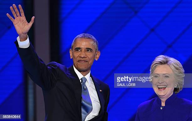 President Barack Obama stands on stage with Democratic presidential nominee Hillary Clinton during Day 3 of the Democratic National Convention at the...
