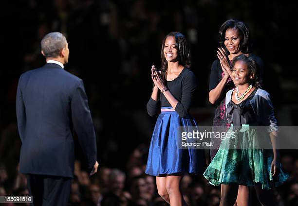 S President Barack Obama stands on stage with first lady Michelle Obama and daughters Sasha and Malia after his victory speech on election night at...