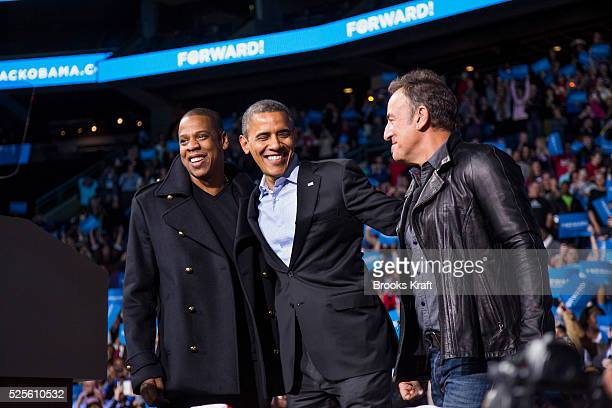US President Barack Obama stands on stage with rapper JayZ and musician Bruce Springsteen at an election campaign rally in Columbus Ohio