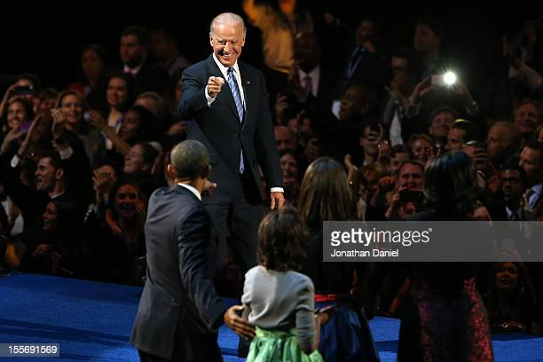 S President Barack Obama stands on stage with Vice President Joe Biden first lady Michelle Obama and daughters Sasha and Malia after his victory...
