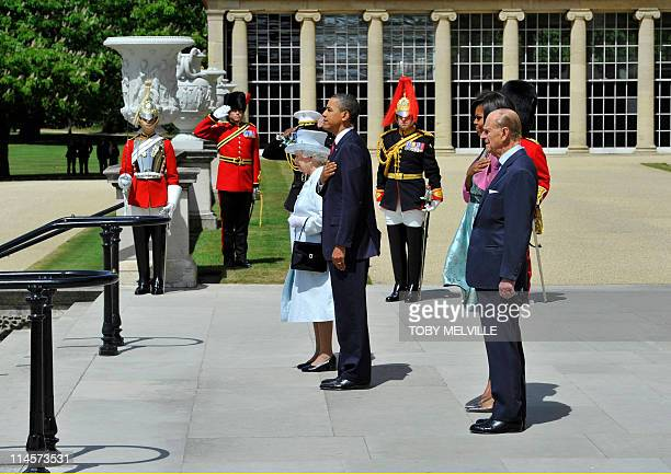 US President Barack Obama stands with Britain's Queen Elizabeth II US First Lady Michelle Obama and Prince Philip as they listen to the US national...