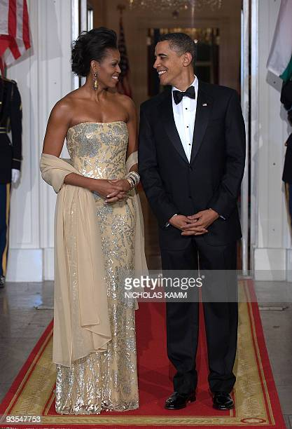 US President Barack Obama stands with First Lady Michelle Obama shortly before greeting Indian Prime Minister Manmohan Singh and his wife Gursharan...