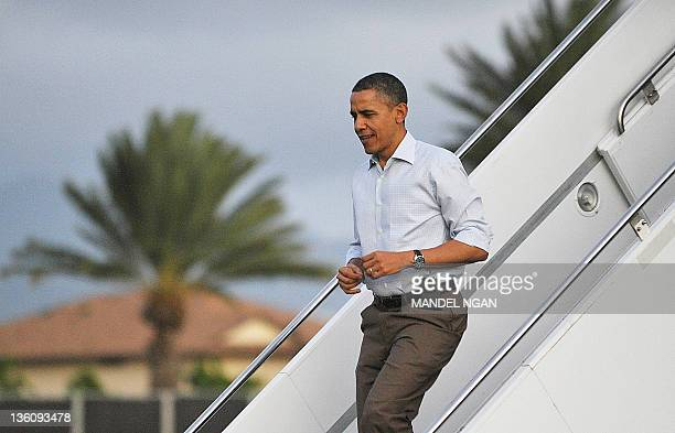 US President Barack Obama steps off Air Force One December 23 2011 upon arrival at Hickam Air Force Base in Honolulu Hawaii Obama was beginning his...