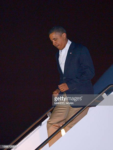 US President Barack Obama steps off Air Force One on January 2 2013 upon arrival at Hickam Air Force Base near Honolulu Hawaii Obama returned to...