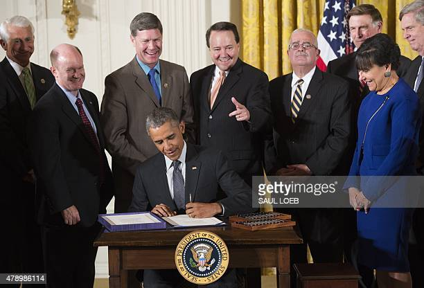 US President Barack Obama surrounded by Cabinet officials and lawmakers signs HR 2146 Defending Public Safety Employees' Retirement Act which...