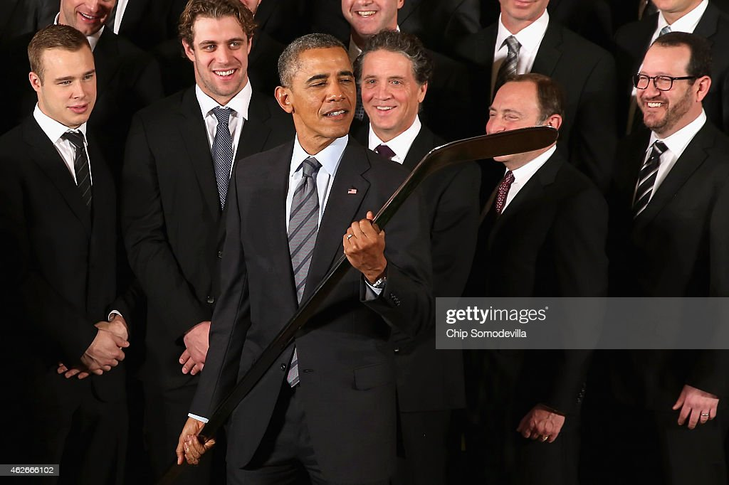U.S. President Barack Obama takes a closer look at the silver hockey stick he was given by the National Hockey League champions Los Angeles Kings in the East Room of the White House February 2, 2015 in Washington, DC. Obama simultaneously hosted the Major League Soccer champions Los Angeles Galaxy. Both teams are owned in part by billionaire and The Weekly Standard publisher Philip Anschutz.