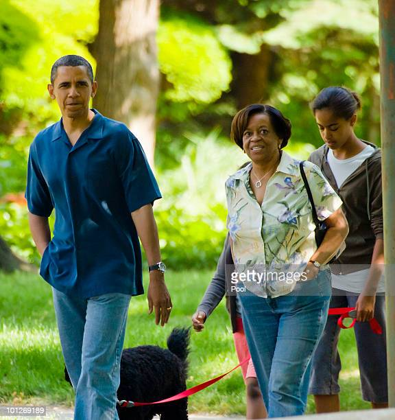 President Barack Obama takes a walk down the street from his home accompanied by his motherinlaw Marian Robinson daughter Malia Obama and dog Bo May...