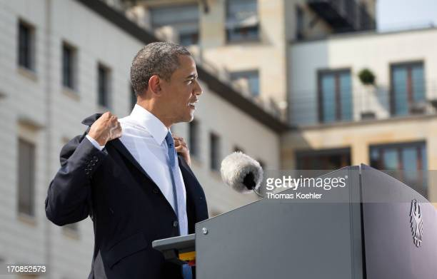 President Barack Obama takes off his jacket as he steps up to make a speech at the Brandenburg Gate on June 19 2013 in Berlin Germany Obama is set to...