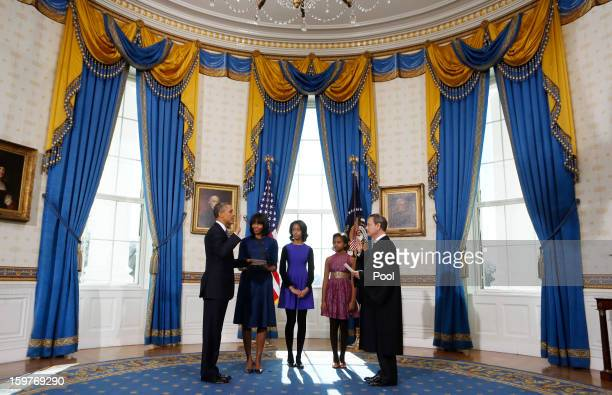 President Barack Obama takes the oath of office from US Supreme Court Chief Justice John Roberts as first lady Michelle Obama holds the bible and...