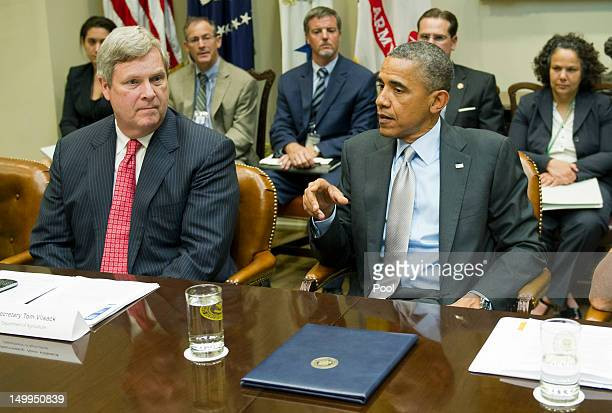 S President Barack Obama talks to Agriculture Secretary Tom Vilsack as he meets with the White House Rural Council to discuss ongoing efforts in...