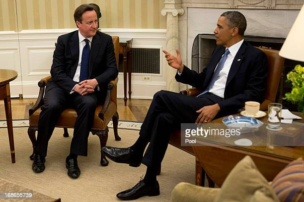 US President Barack Obama talks to British Prime Minister David Cameron in the Oval Office of the White House May 13 2013 in Washington DC Cameron...