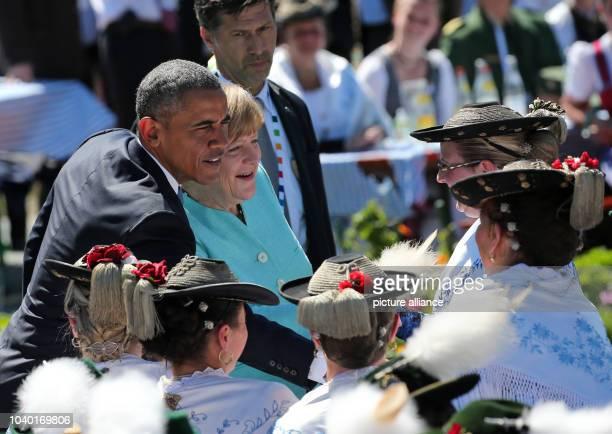 President Barack Obama talks to members of the public in traditional dress in Kruen, Germany, 07 June 2015 with German Chancellor Angela Merkel...