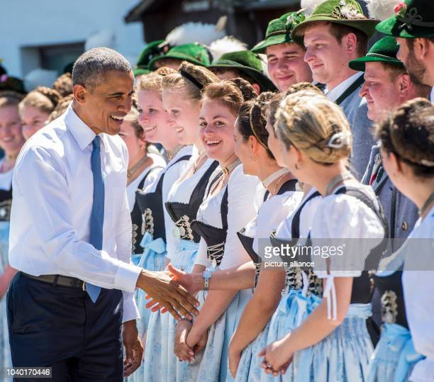 President Barack Obama talks to members of the public in traditional dress in Kruen, Germany, 07 June 2015 as he joins with German Chancellor Angela...