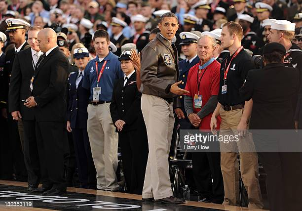 S President Barack Obama talks to people courtside before the start of the NCAA men's college basketball Carrier Classic between the Michigan State...