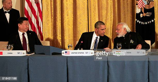 President Barack Obama talks to Prime Minister Narendra Modi of India as President Xi Jinping of the People's Republic of China looks on at the...
