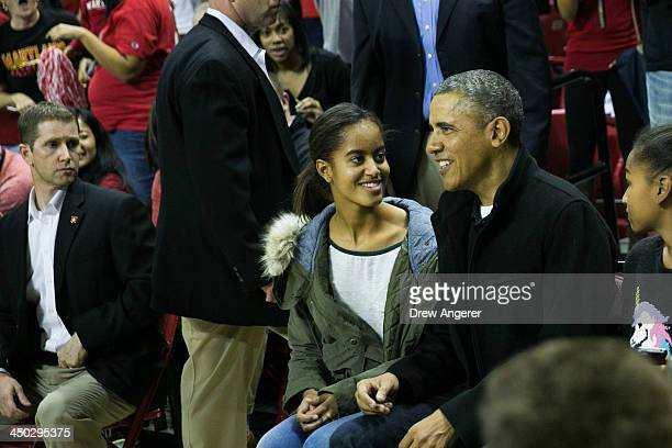 President Barack Obama talks with daughter Malia Obama as they attend a men's NCCA basketball game between University of Maryland and Oregon State...