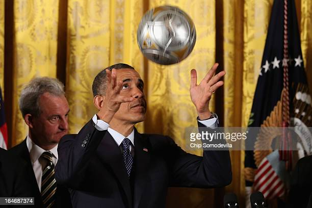 S President Barack Obama throws a ball into the air before bouncing a soccer ball on his head during a ceremony honoring players and coaches from the...