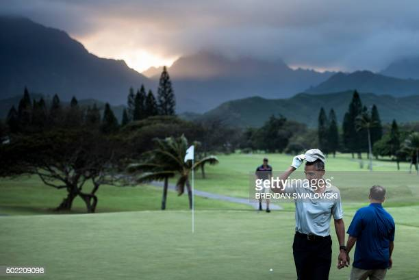 President Barack Obama tips his hat to onlookers after chipping a ball in on the 18th green21 of the Mid-Pacific Country Club's golf course December...