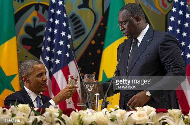 US President Barack Obama toasts with Senegal President Macky Sall during an official dinner at the Presidential Palace in Dakar on June 27 2013...