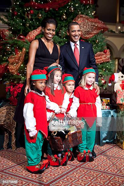 US President Barack Obama top right and First Lady Michelle Obama pose with children dressed as elves at the Christmas in Washington concert at the...
