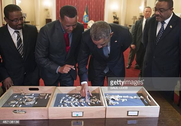 US President Barack Obama touches a bone fragment of 'Lucy' who was estimated to have lived 32 million years ago alongside Ethiopian Prime Minister...