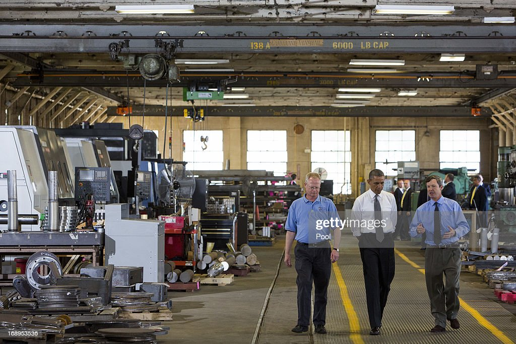 U.S. President Barack Obama (C) tours Ellicott Dredges, a manufacturing facility, with CEO Peter Bowe (R) on May 17, 2013 in Baltimore, Maryland. Obama's visit to Baltimore includes a visit to an elementary School, a manufacturing plant and a local community center.