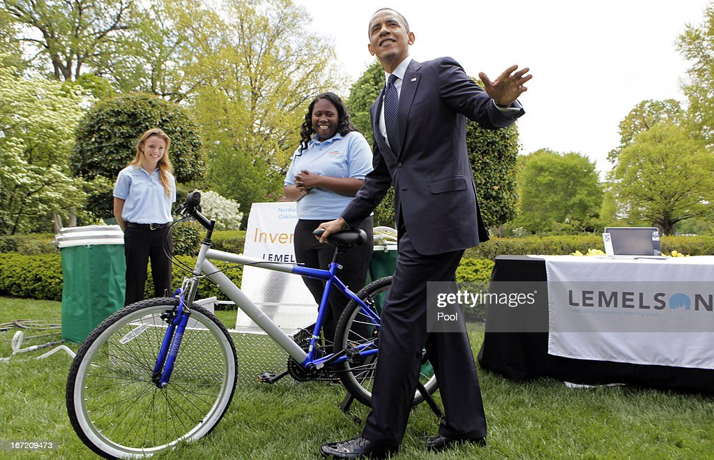 U.S. President Barack Obama tries the bicycle-powered emergency water-sanitation station, created and presented by high schoolers Payton Karr (L) and Kiona Elliot (R) from Oakland Park, Florida, in the East Garden of the White House, during the White House Science Fair April 22, 2013 in Washington, DC. The White House Science Fair celebrates the student winners of a broad range of science, technology, engineering and math (STEM) competitions from across the country. The first White House Science Fair was held in late 2010.