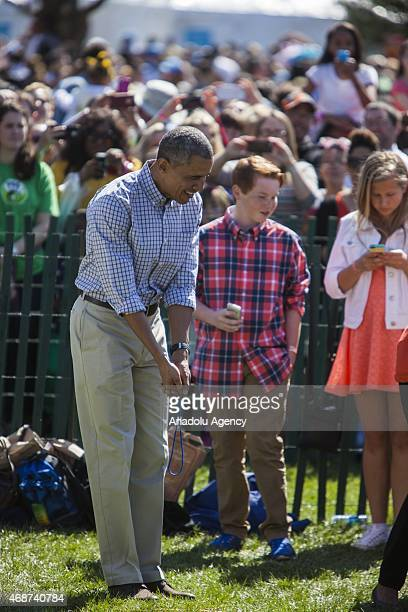President Barack Obama tries to show a boy that he should use a golf swing to push his colored easter egg to the finish line during the annual White...