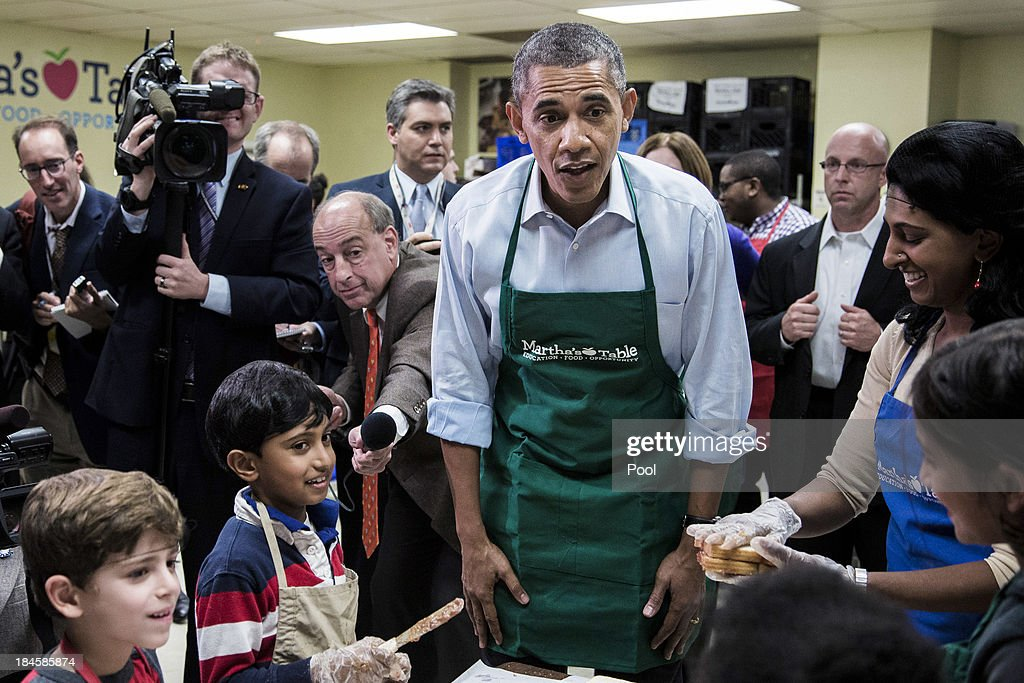U.S. President Barack Obama visits with furloughed federal workers volunteering at a Martha's Table kitchen on October 14, 2013 in Washington, D.C. During a statement, Obama called on congress to end the budget stalemate and allow federal employees to return to work.