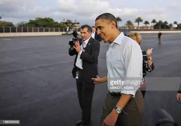 US President Barack Obama walks across the tarmac to greet wellwishers December 23 2011 upon arrival at Hickam Air Force Base in Honolulu Hawaii...