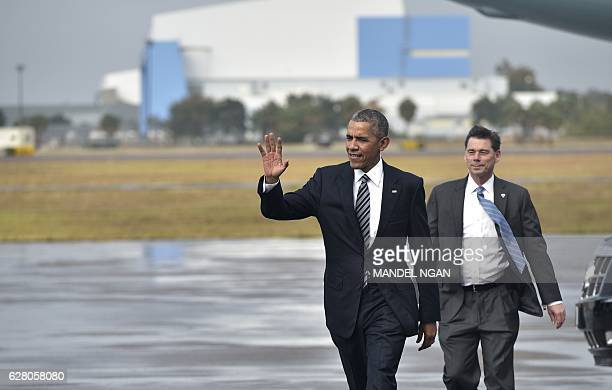 US President Barack Obama walks across the tarmac to greet wellwishers upon arrival at Tampa International Airport in Tampa Florida on December 6...