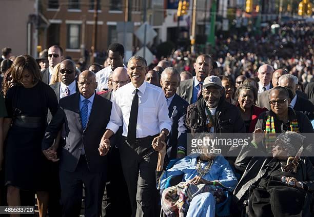 US President Barack Obama walks alongside Amelia Boynton Robinson one of the original marchers First Lady Michelle Obama and US Representative John...
