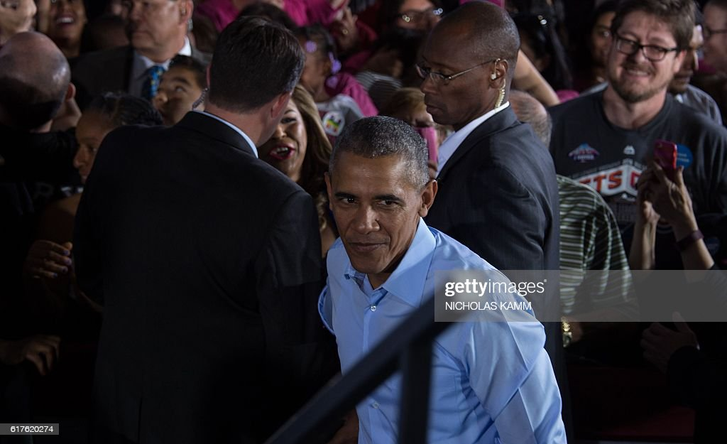 US President Barack Obama walks back onto the stage after shaking hands following his speech at a campaign event for Democratic presidential candidate Hillary Clinton in Las Vegas on October 23, 2016. / AFP / NICHOLAS